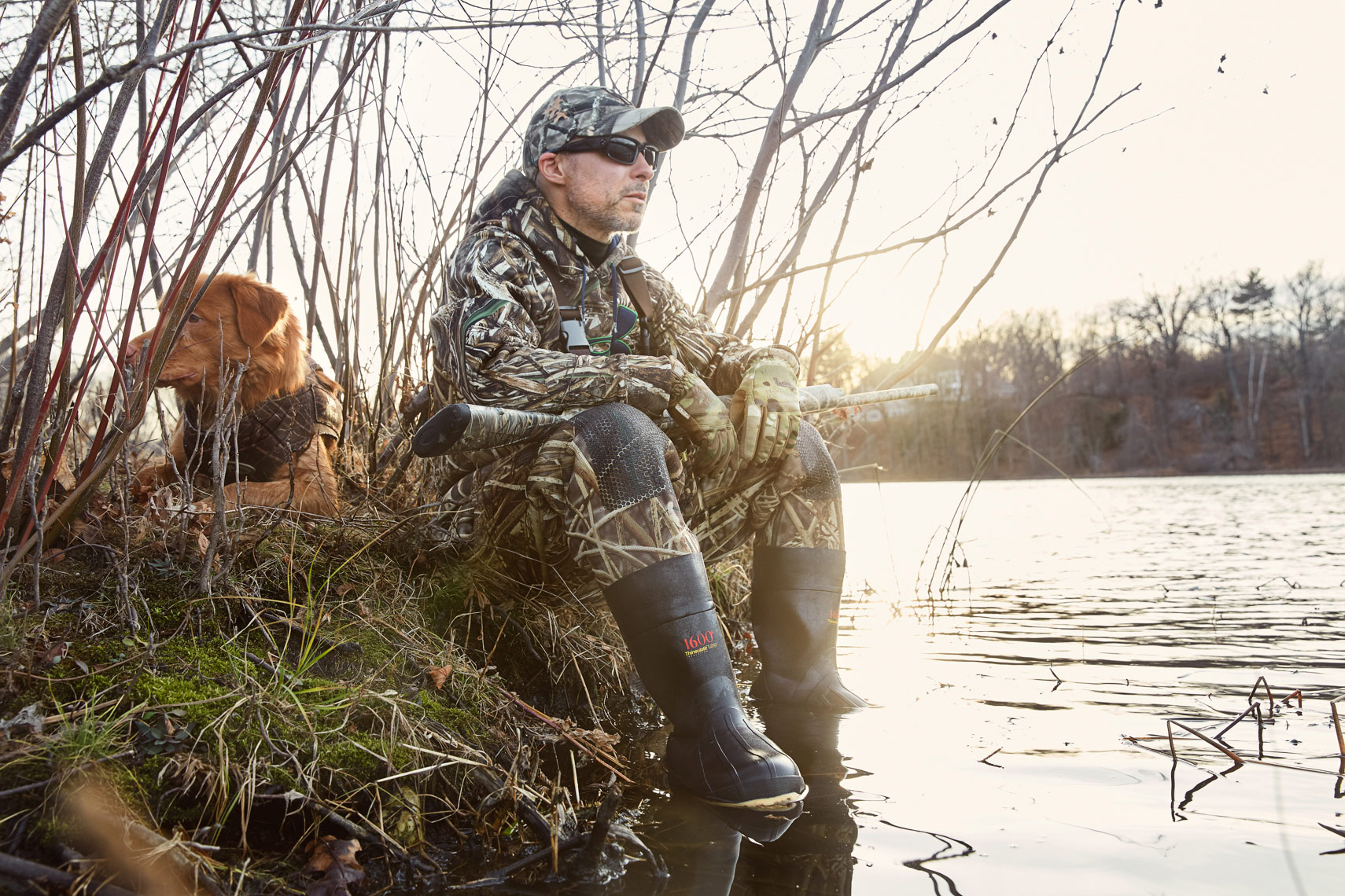 Fowl hunter in under armor camouflage with his hunting dog
